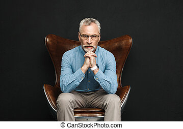 Portrait of businesslike gentleman 50s with grey hair and beard in glasses sitting on wooden armchair with severe look, isolated over black background