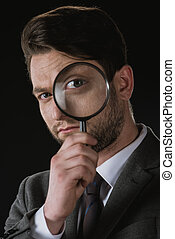 portrait of businessman holding magnifying glass isolated on black