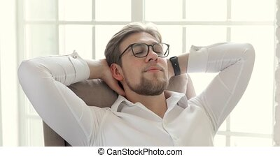 Portrait of businessman in glasses resting in his chair near...