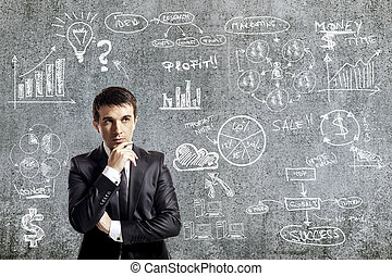 portrait of businessman in suit and business plan on grunge wall