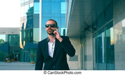 Portrait of businessman in sunglasses talking on phone and walking in street. Young man having business conversation during commuting to work. Confident guy in suit being on his way to office building