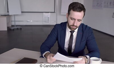 Portrait of businessman is reading a report in conference room in the modern office.