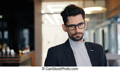 Portrait of businessman looking at camera with serious face standing in cafe