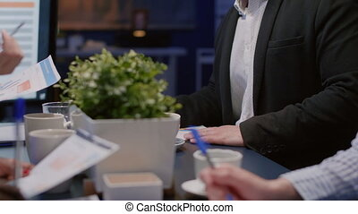 Portrait of businessman looking into camera sitting at conference table working in meeting room late at night. Diverse multi ethnic teamwork analyzing company marketing strategy brainstorming ideas