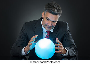 Portrait Of Businessman Predicting Future With Crystal Ball...