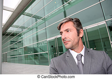 Portrait of businessman standing in front of modern building