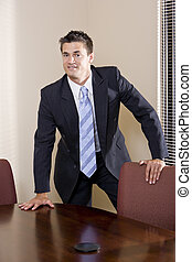 Portrait of businessman wearing suit in boardroom