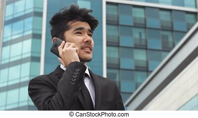 Portrait of businessman who makes phone calls standing in...