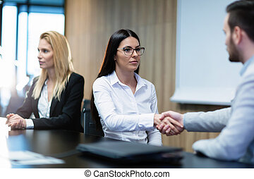 Portrait of businesswoman shaking hands with colleague