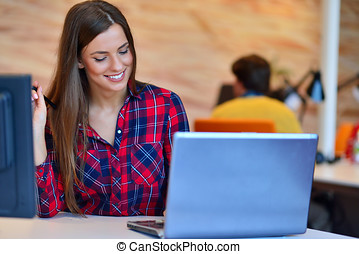 Portrait of businesswoman smiling while sitting by colleagues in office