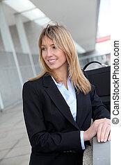 Portrait of businesswoman waiting outside a building