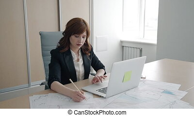Portrait of businesswoman working with laptop and paper...