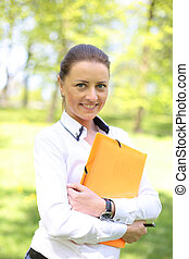 Portrait of busy sales woman at park - Portrait of busy...