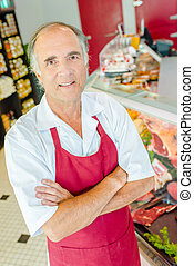 Portrait of butcher in store with arms crossed