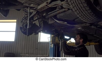 Portrait of car mechanic working with hammer under automobile in auto repair