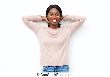 carefree young black woman smiling with hands behind head against white background