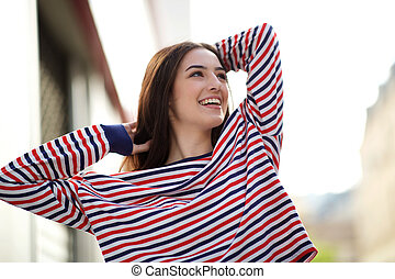 carefree young woman smiling with hand in hair