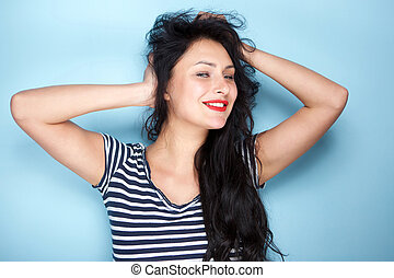 carefree young woman smiling with hands in hair