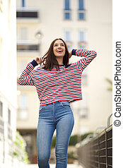 carefree young woman walking in town with hands in hair