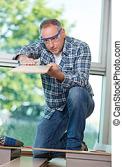 portrait of carpenter checking flatness of wooden plank