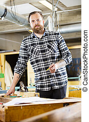 Portrait of carpenter planning work in the workshop - ...