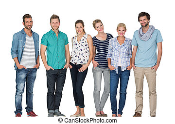 Group portrait of casual happy people standing with hands in pockets over white background