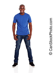 portrait of casual young african man standing on white...