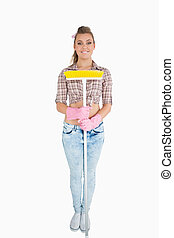 Portrait of casual young woman holding broom