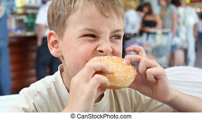 caucasian boy eating hamburger in cafe