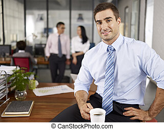 successful caucasian expat businessman sitting on desk in office with local colleagues talking in background.