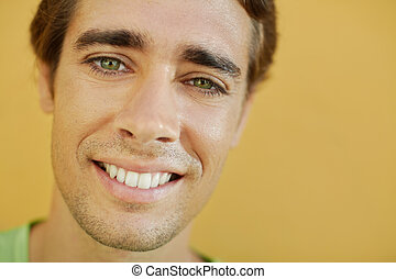 portrait of caucasian college student smiling and looking at camera with yellow wall in background. Selective focus, copy space