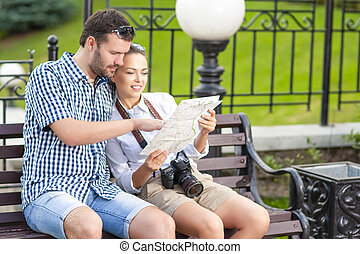 Portrait of Caucasian Couple Travelling Together with Photocamera. Discussing Route Using City Map Outdoors Together Embraced.