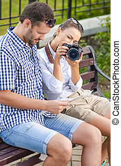 Portrait of Caucasian Couple Travelling Together with Photocamera. Female Pointing Camera Straight to Viewer. Using City Map Outdoors Together.