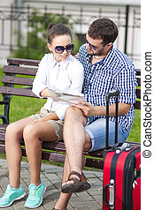 Portrait of Caucasian Couple Travelling Together with Trolley. Checking and Discussing Route Using City Map Outdoors.