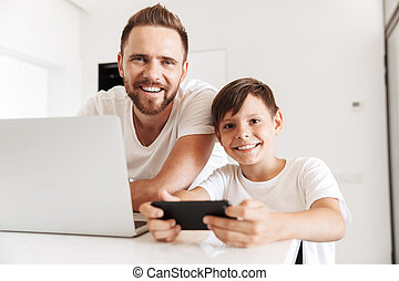 Portrait of caucasian father 30s and son 8-10 smiling at camera together at home, while using silver laptop and playing games on smartphone