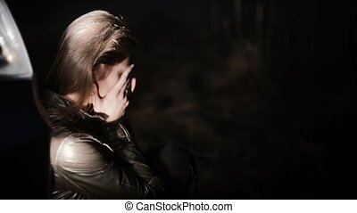 Portrait of Caucasian girl crying after bad news. Beautiful shocked female near car headlight covering face with hands.