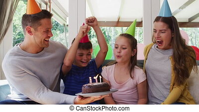 Portrait of caucasian girl in party hat blowing candles on birthday cake while family smiling and waving looking at the camera at home. social distancing during coronavirus quarantine lockdown.