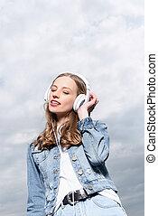 portrait of caucasian girl listening music in headphones outdoors