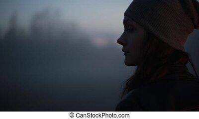 Portrait of Caucasian girl walking away into fog. Beautiful...
