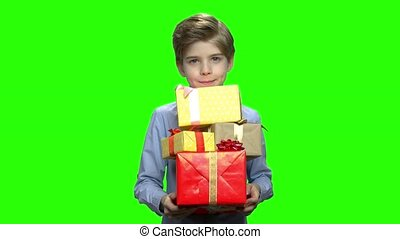 Portrait of caucasian kid holding gift boxes.