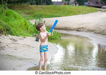 Portrait of caucasian little boy in straw hat playing toys and water pump on the beach.
