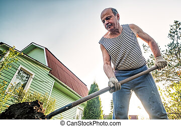 Portrait of caucasian male farmer with shovel digging the land in the country house