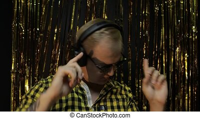 Portrait of caucasian man dancing on black background. Gold shining foil strips. Party, music, disco