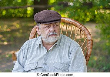 Portrait of Caucasian senior man sitting in a chair in summer park