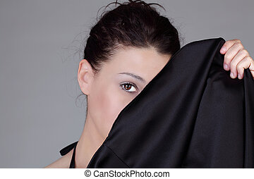 Portrait of caucasian woman holding skirt across face