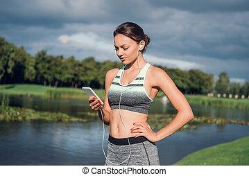 woman in earphones using smartphone