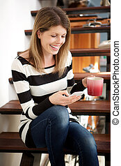 caucasian woman sitting on stairs and using smart phone at home