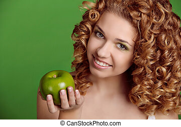 Portrait of Caucasian young woman with apple. over green