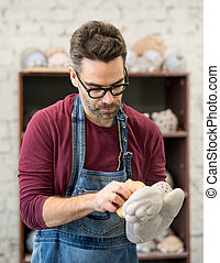 Portrait of Ceramist Dressed in an Apron Working on Clay Sculpture in Bright Ceramic Workshop.