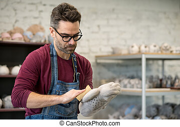 Portrait of Ceramist Dressed in an Apron Working on Clay...